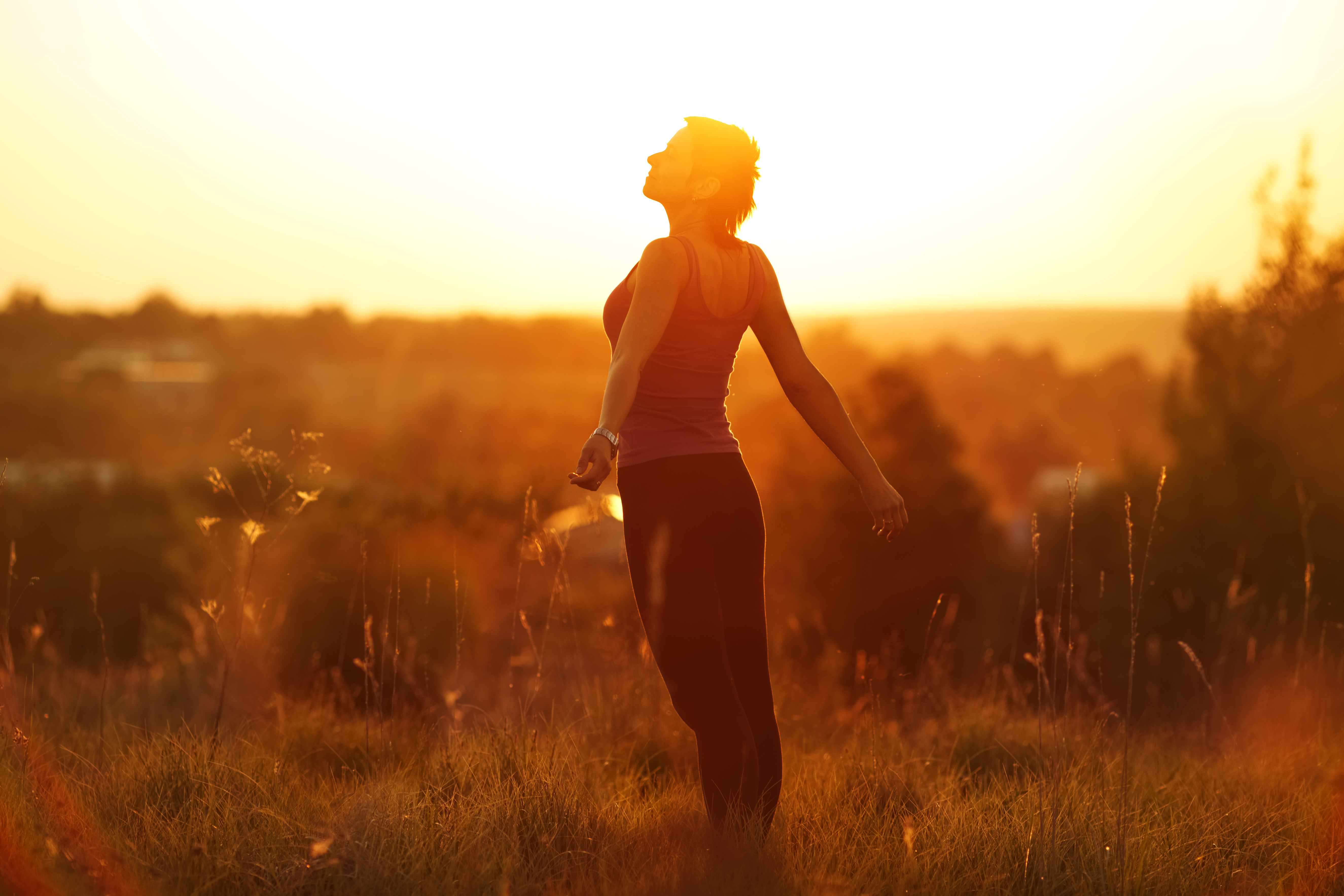 Fit happy woman in a field at sunset